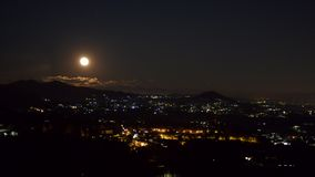 The sky with the full moon. The rising of the full moon, in the sky behind the small village of Sordevolo stock video