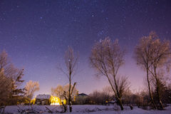 Sky full of stars above snowy winter village Stock Images