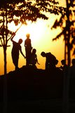 Silhouettes of kids playing on a hill, under trees, during sunset. The sky is full of yellow/ orange hue of sunset hour and the rest of the scenery: kids playing Stock Photography