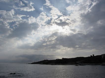 Sky with giants cumulonimbus clouds and silhouette of the tuscan coastline Stock Images
