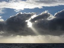Sky with giants cumulonimbus clouds and sun rays through over the sea Stock Images