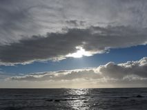 Sky with giants cumulonimbus clouds and sun rays through over the sea Royalty Free Stock Photo