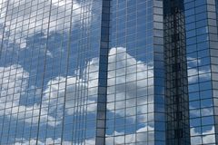 Sky and Glass. The sky mirrired in the reflections on a modern glass and steel building Stock Images