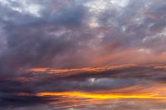 Sky with gray and blue clouds and red-orange highlight from the Sun, background.  Royalty Free Stock Photos