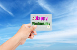 Sky. Hand give paper write happy Wednesday on blue sky background stock photography