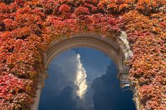 Sky with heavy storm clouds. Seen through the arch covered with red ivy leaves Stock Photography
