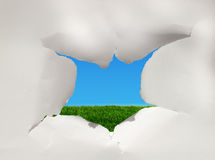 Sky hole. A hole torn in a peice of paper with sky and grass showing through royalty free stock image