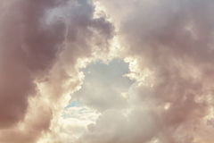Sky. Hole in fluffy clouds with soft pink light Stock Images