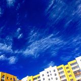 Sky and house. Sky blue yellow house clouds Stock Image