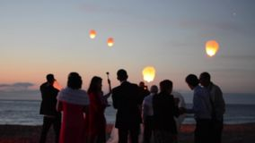 Sky lantern flying in night sky.  Slow motion footage. Happy silhouette people celebrating wedding on the beach. Blurred background stock footage