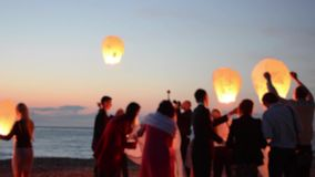 Sky lantern flying in night sky.  Slow motion footage. Happy silhouette people celebrating wedding on the beach. Blurred background stock video footage