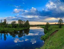 Sky with light clouds reflected in the river. Field, trees, summer evening Royalty Free Stock Photos