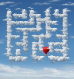 Sky Is The Limit. Concept with a red hot air balloon flying up to the sky navigating through a group of storm clouds in the shape of a maze or labyrinth puzzle Royalty Free Stock Photography