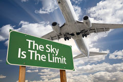 The Sky Is The Limit Green Road Sign and Airplane Stock Photography