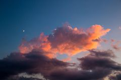 Sky with Moon and rose Clouds during Sunset Stock Images