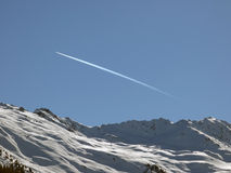 Sky. Mountains and a Flying Airplane above Stock Image