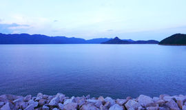 Sky, mountains, stone wall and peaceful lake Royalty Free Stock Image