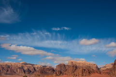 Sky and mountains in Wadi Rum,. Mountains and sky with sparse clouds in Wadi Rum desert reservation, Jordan royalty free stock photos