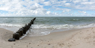 Sky and Ocean - a panorama. Blue Sky, seashore and deep ocean - with old pier pillars Stock Photo