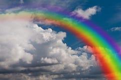 Sky, oklarheter och regnbåge. Arkivfoto
