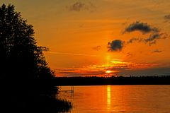 Sky Over Bass Lake Lit By Sunset Colours. Sunset on Bass Lake in the Kawartha Lakes region of Ontario, Canada stock photo