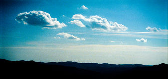 Sky over hills. Deep blue sky with cumulus clouds over hills silhouettes; 35 mm scan, visible grain Stock Photography
