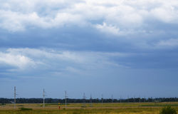 Sky over Temryuk. Adjacent field near the road with power poles and heavily overcast sky preparing to precipitation royalty free stock photography