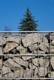 Sky and pine in the background. In the foreground a gabion filled with granite debris. stock photos