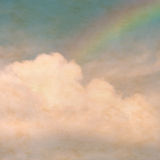 Sky rainbow clouds on a textured, vintage paper background with. Grunge stains Royalty Free Stock Photography