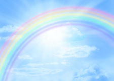 Sky Rainbow Sun Background. A rainbow in a light blue sky with clouds and sunbeams stock photography