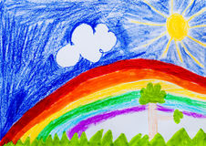 Sky and rainbow. Sun and trees. Child drawing. Drawing with wax crayons. Colorful rainbow in the blue sky. Big sun, grass and tree. Drawing made by the hands of Stock Photography