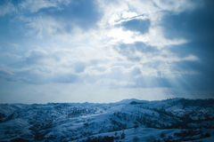 Sky rays. Landscape shot of a mountain range covered in snow under a cloudy sky with the sun's rays beaming down Royalty Free Stock Photo