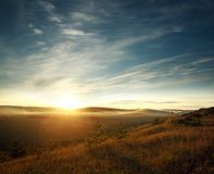 Sky in rays of setting sun over the hills and fields Royalty Free Stock Image