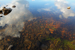 The sky is reflected in shallow backwater. The bottom of the lake with a lot of stones and reflected sky royalty free stock photos