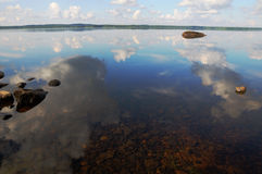The sky is reflected in shallow backwater. The bottom of the lake with a lot of stones and reflected sky royalty free stock image