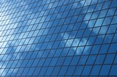 Sky reflecting in windows of office building royalty free stock photos