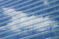 Sky Reflection in Office Building Glass. Glass office building with reflection of summer sky Stock Image