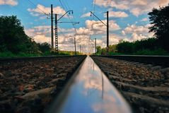 Sky reflection on railroad tracks stock images