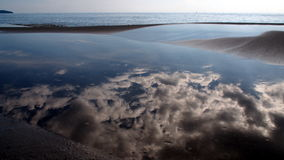 Sky Reflection. In a sea puddle at Serendipity beach, Sihanoukville, Cambodia Royalty Free Stock Photo