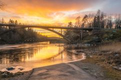 Sky reflection on the water under the bridge. Colourful sky on the water under the bridge in the evening on sunset time stock image