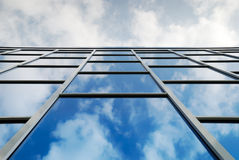 Sky reflection in window. Reflection of a cloudy sky in glass wall of an office building Stock Photos