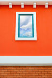 Sky reflection in window glass on orange wall Stock Photos