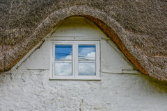 Sky reflection in the window of an old house. In UK many things are old. In the old window, is reflected the sky of some new times. The roof, like many other Royalty Free Stock Image