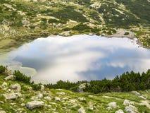 Sky reflections on the Fish Lake water surface, Seven Rila Lakes, Rila Mountains, Bulgaria royalty free stock image