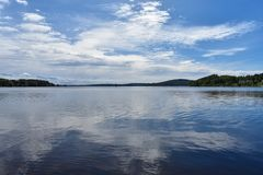 Sky reflects into the lake`s surface. Sunny summer day royalty free stock photography