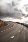 Sky Road Curve. Beautiful gray sky road curve on the mountains Royalty Free Stock Photography