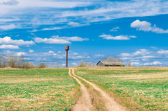 Sky road in the field leading to the shed barn and water tower of the rural landscape of the village. Stock Images