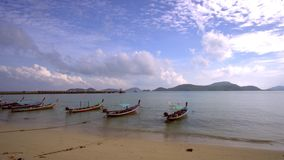 Sky and Sand of Beach Andaman Sea. White clouds and traditional Thai boats - longboat on the water. 4K stock footage