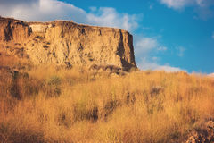 Sky and sandy cliff. Ground and dry grass. Go breathe fresh air. Rest from the noise Stock Photos