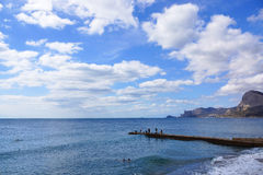 The sky, the sea, the fishermen. Sudak. Crimea. Skyscape.beautiful clouds in the blue sky over the sea.Fishermen on the pier fishing Stock Photo